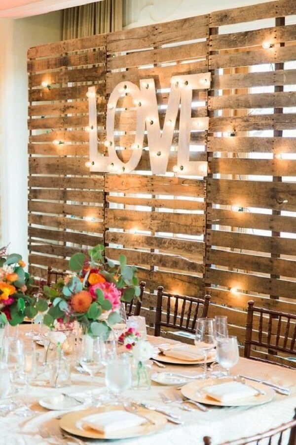 Pallet panel and lights are part of simple wedding decoration