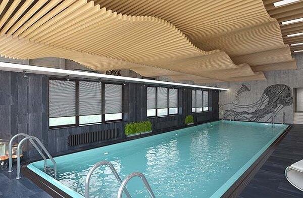 Porcelanato escuro reveste o piso dessa piscina coberta