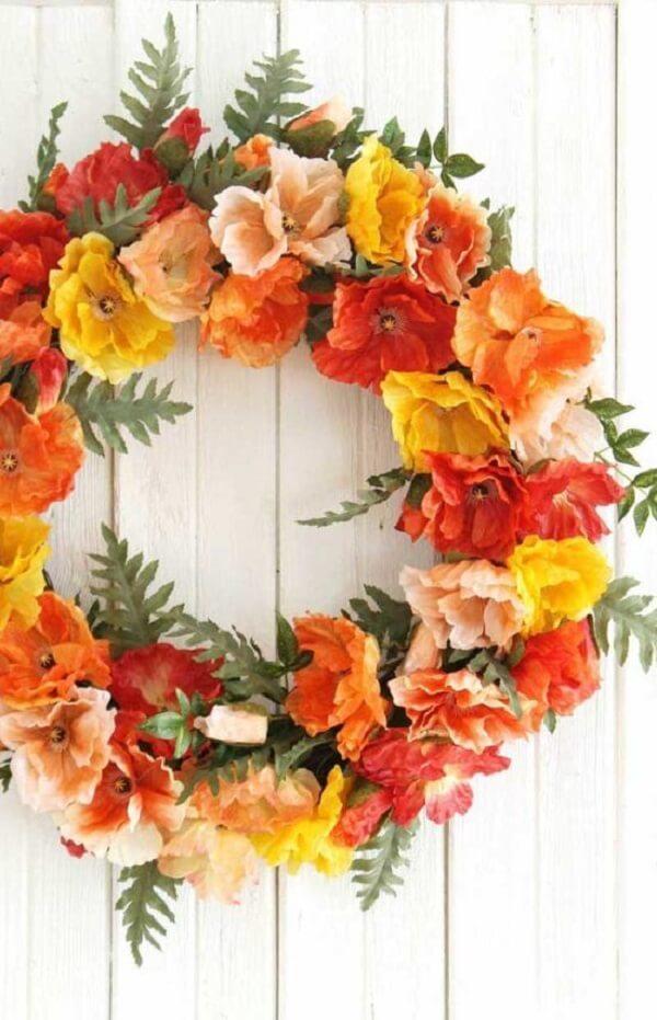 Quebre a neutralidade da porta branca com uma linda guirlanda de flores artificiais