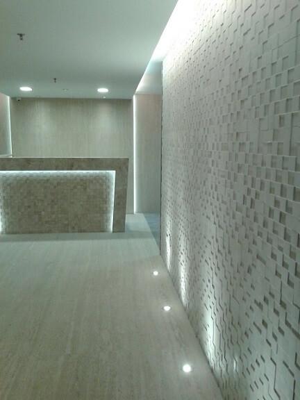 Recepção de clínica com mosaico de mármore travertino Projeto de Evely Bengio