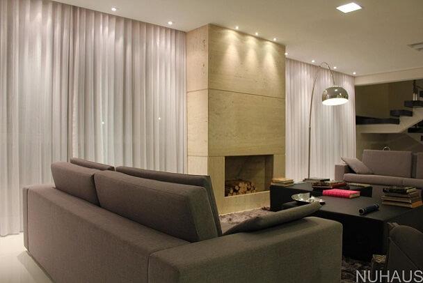 Sala de estar com lareira de mármore travertino Projeto de Nuhaus