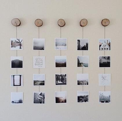 Varal de fotos penduradas em tocos de madeira