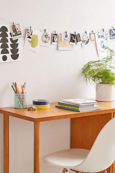 Varal de fotos sobre mesa de estudos