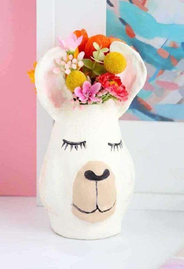Vaso criativo e flores artificiais coloridas alegram o ambiente