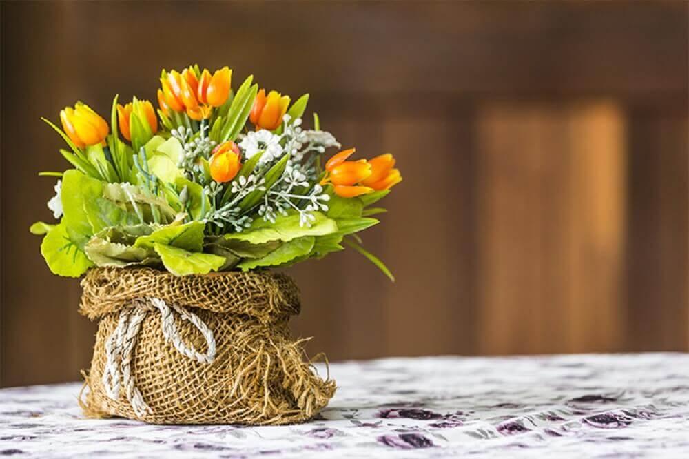 arranjos de flores artificiais em saco de estopa