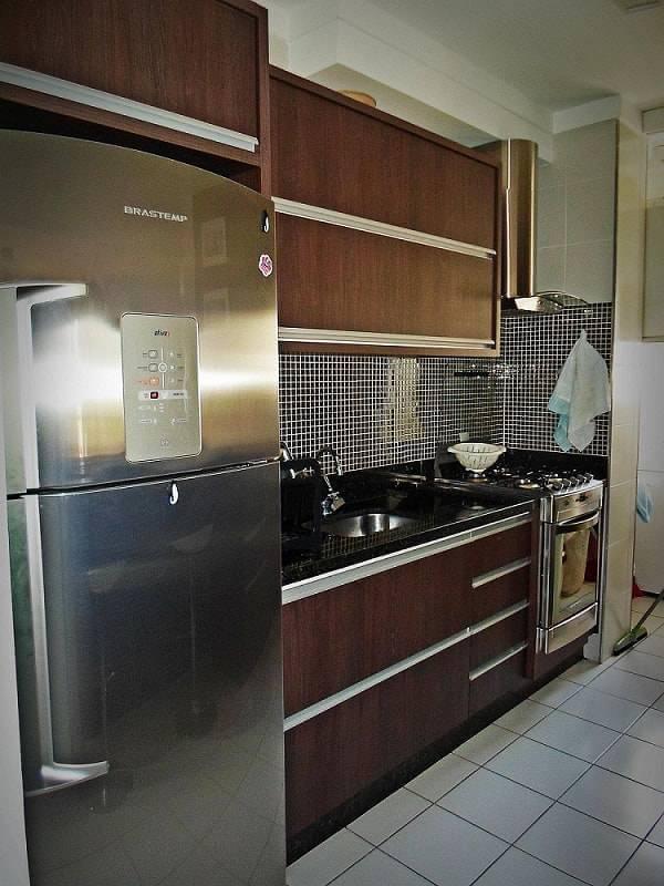 Cozinha decorada com gabinete escuro e pastilhas para cozinha
