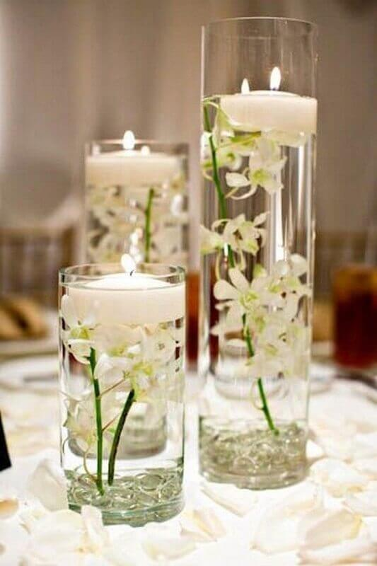 wedding decoration with vases of water with flowers and candles