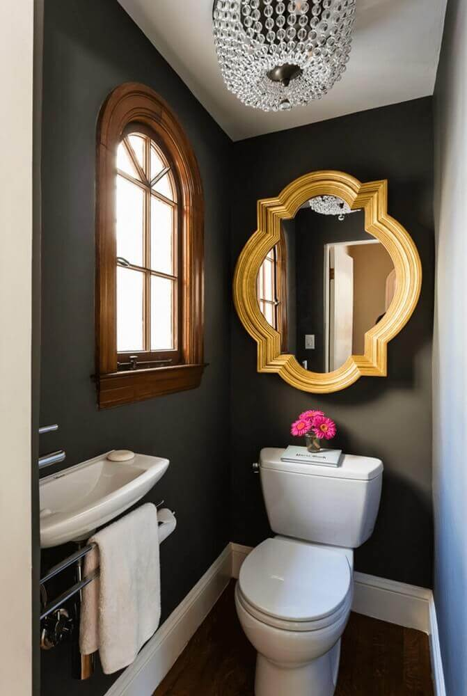 decoração de lavabo pequeno com parede preta e espelho dourado