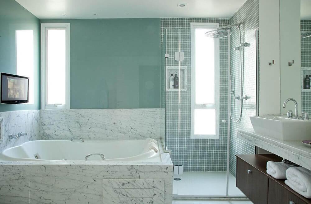Banheiro com banheira e box separado.