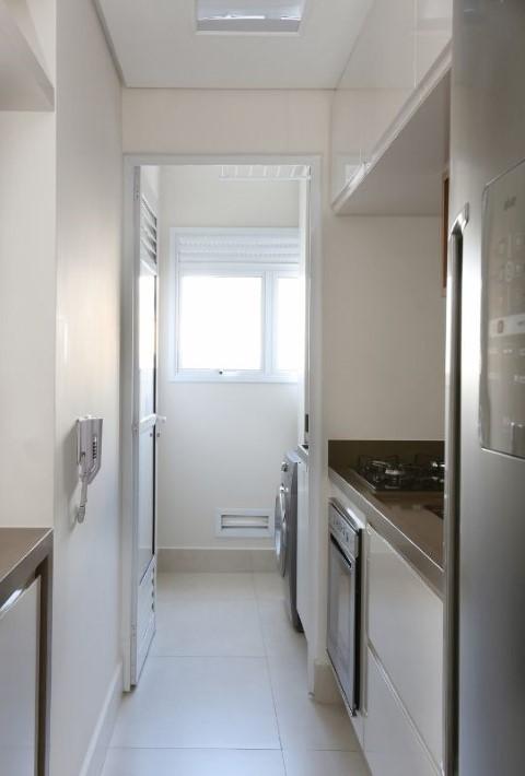 Área de serviço separada da cozinha por porta Projeto de Bianchi Lima