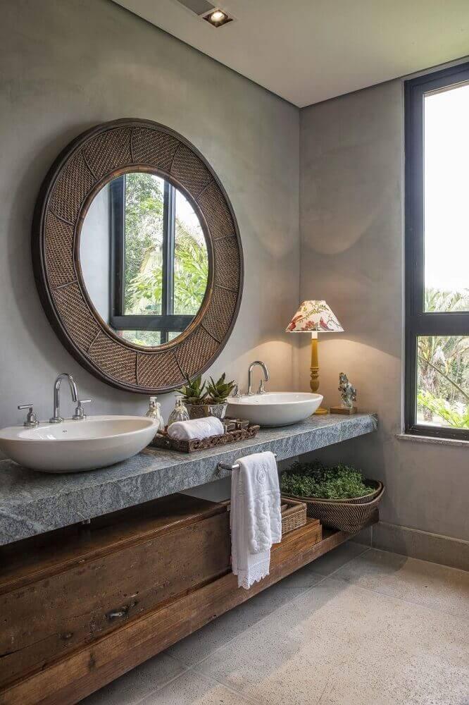 decoração de lavabo com espelho redondo e parede de cimento queimado.