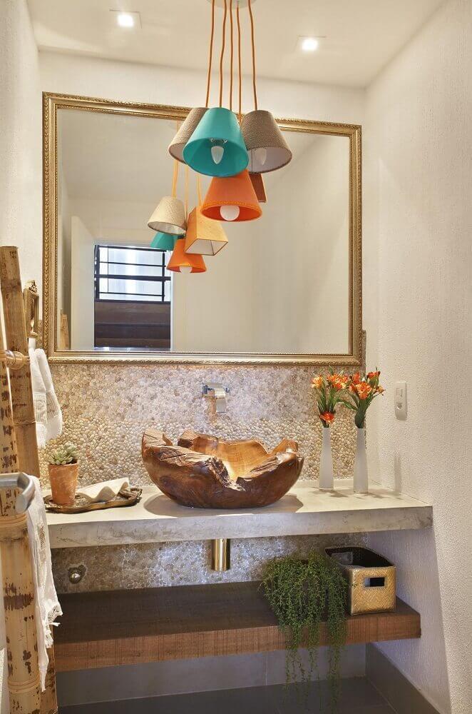 decoração de lavabo pequeno com cuba de madeira e pendentes coloridos.