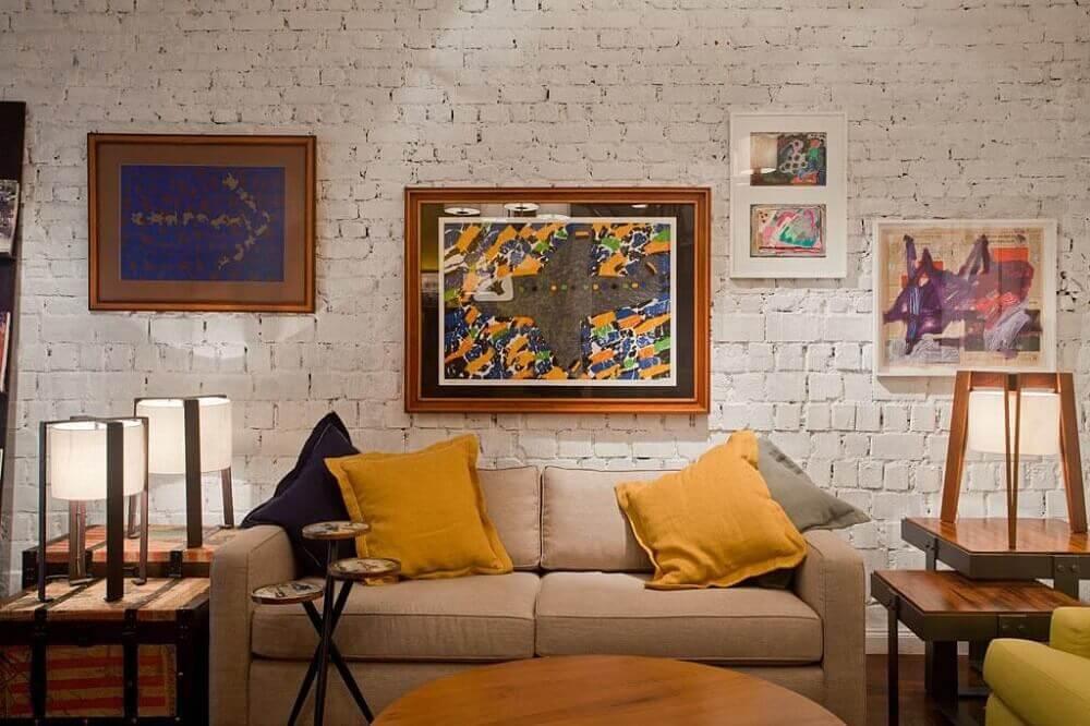 Sala com parede de tijolinho branco e quadros