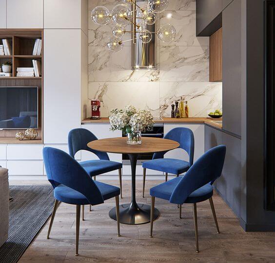 Mesa de jantar pequena com cadeira azul e lustre moderno