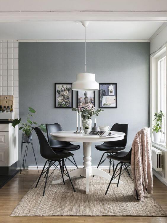 Mesa de jantar pequena com cadeira preta e detalhes neutros