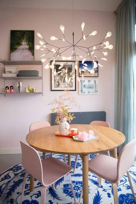 Mesa de jantar pequena e redonda com lustre moderno acima