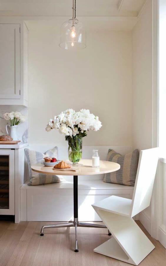 Mesa de jantar pequena decorada com vaso de flores