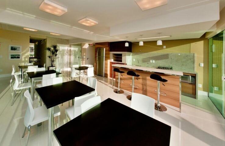 Área de lazer com churrasqueira e várias mesas Projeto de Juliana Pippi