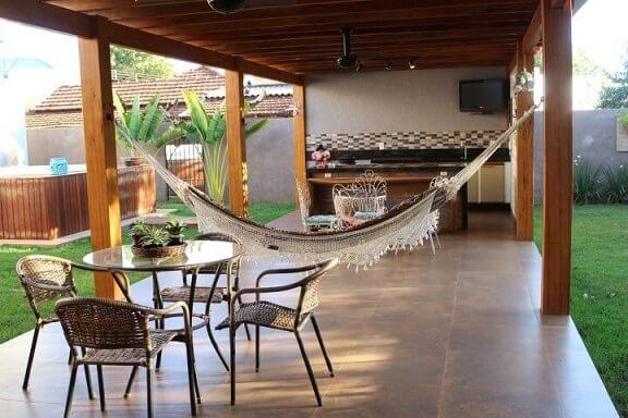Área de lazer com churrasqueira, rede e piscina Projeto de Bianca Monteiro