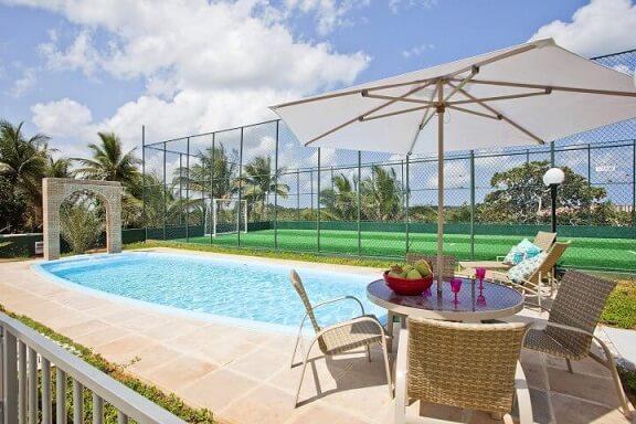 Área de lazer com piscina e móveis na beirada Projeto de Vanja Paes
