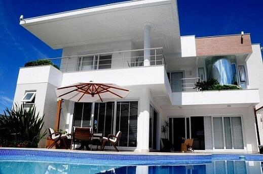 Área de lazer com piscina e mesa com ombrelone Projeto de Juliana Pippi