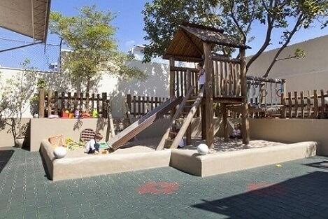 Área de lazer com playground de madeira Projeto de Adelle Porto