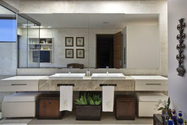 Banheiro de luxo com quadros, puffs, planta e mais. Projeto de Eduarda Correa
