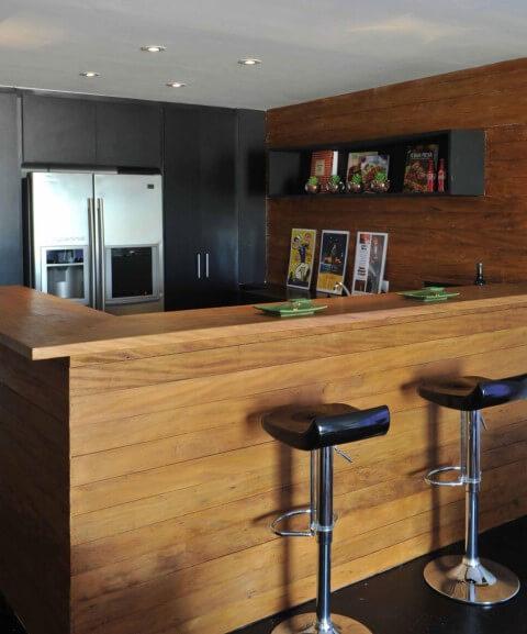 Bar em casa com bancada de madeira Projeto de Deborah Roig