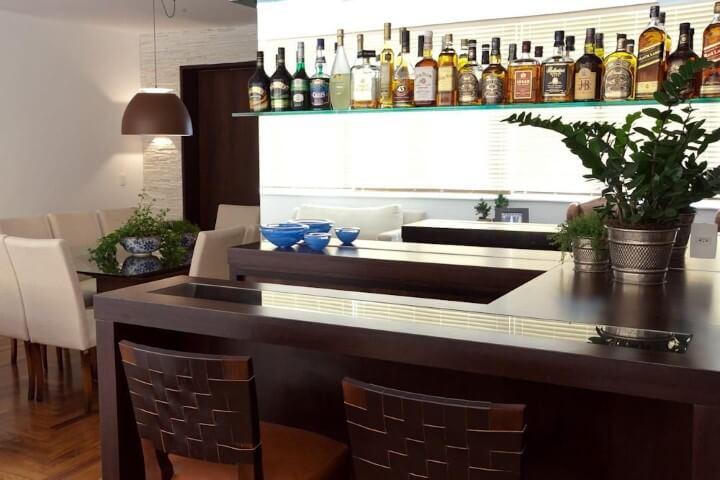 Bar em casa com bancada de madeira e prateleira de vidro Projeto de Lucila Bertoncello