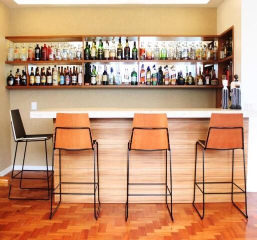 Bar em casa com bancada e banquetas Projeto de Mallemont Arquitetura
