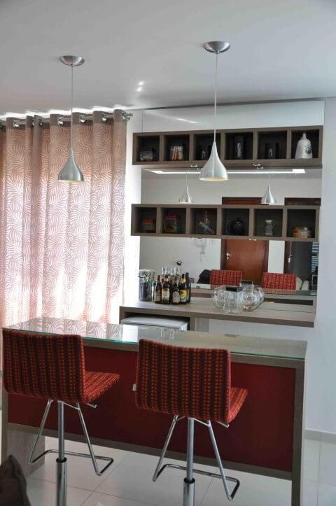 Bar em casa com bancada e banquetas vermelhas Projeto de Claudia Breias