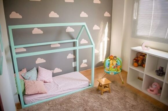 Cama montessoriana em quarto com parede de nuvens Projeto de Ana Branco