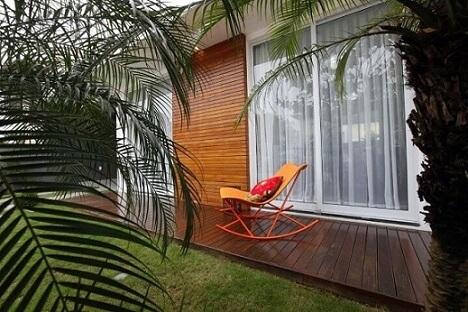 Casa com varanda com cadeira de balanço Projeto de Cristina Rei