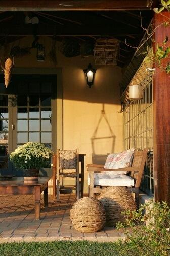 Casa com varanda com piso de tijolo e móveis rústicos Projeto de Katia Perrone