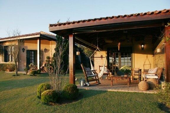 Casa com varanda com rede e cadeira de balanço Projeto de Katia Perrone