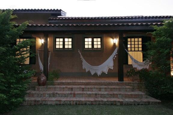 Casa com varanda com redes e arandelas Projeto de Katia Perrone