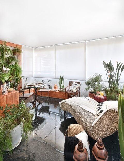 Casa com varanda decorada com vasos de plantas e chaise Projeto de Tetriz Arquitetura