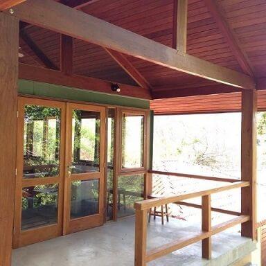 Casa com varanda e portas de vidro Projeto de Cals Arquitetos