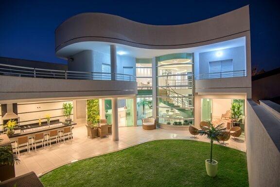Casa com varanda gourmet com balcão e banquetas Projeto de Aquiles Nicolas Kilaris
