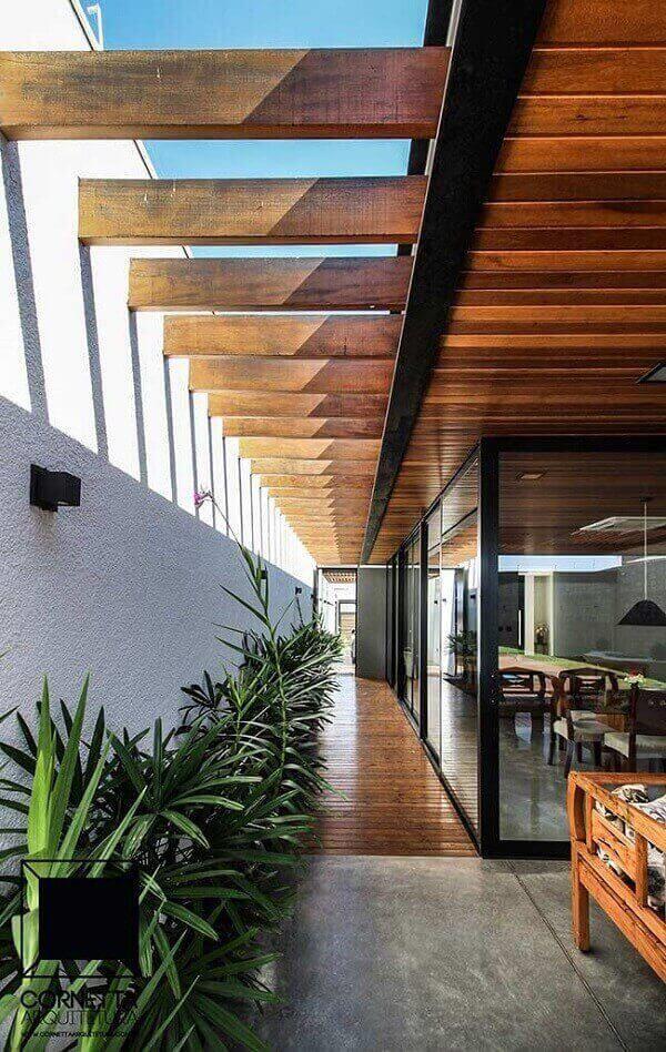 Corredor extenso com piso de madeira e folhagens