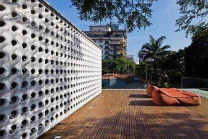 Deck de madeira na piscina com puffs Projeto de Studio MK27