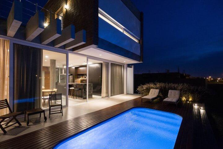 Deck de madeira perto de piscina iluminada Projeto de Eduardo Paiva