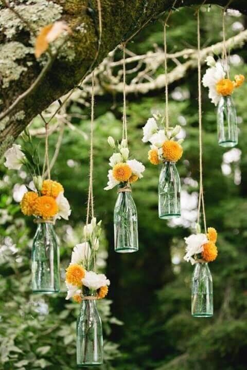 Decoração de aniversário simples com garrafas como vaso de flores