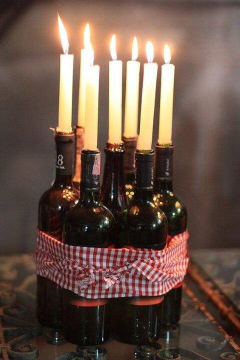 Decoração de aniversário simples com garrafas de vinho com velas