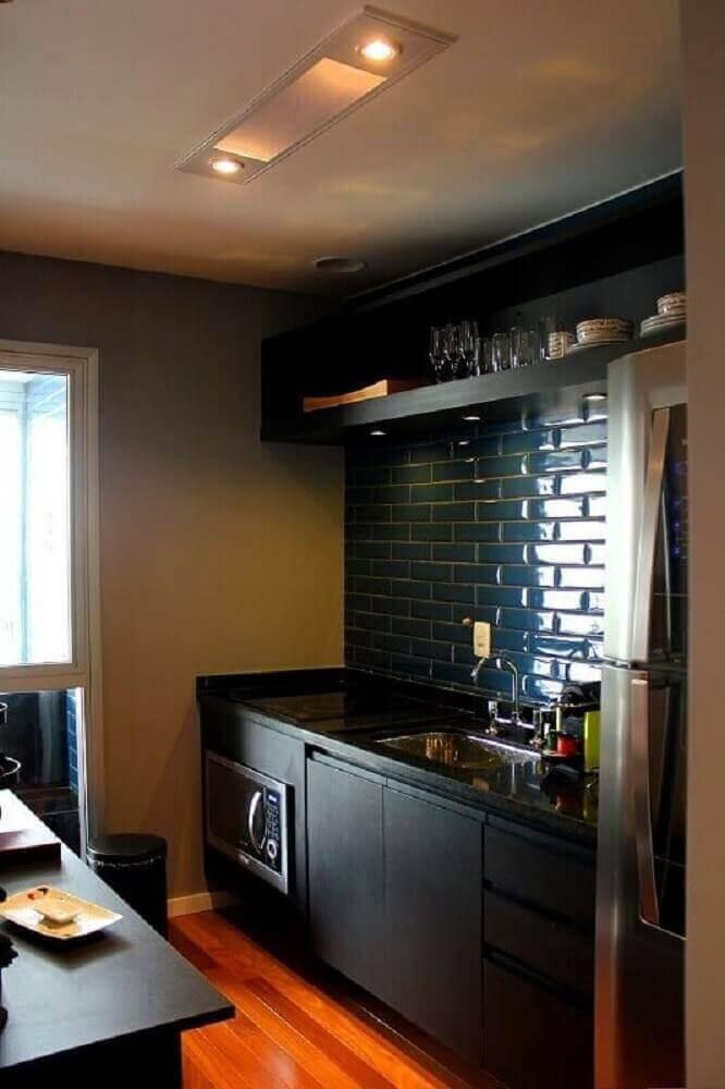 Cozinha planejada preta com ladrilho hidráulico e piso de madeira