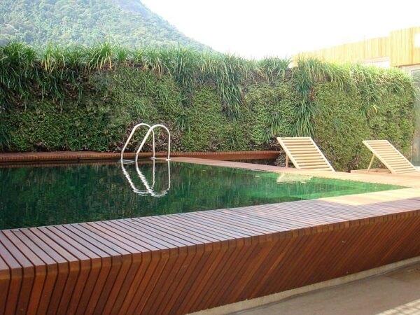Piscina com borda infinita estruturado com deck de madeira