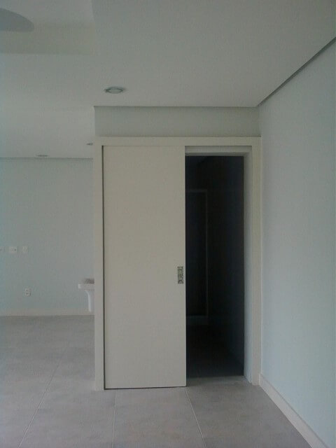 Porta de correr branca na sala Projeto de Margareth Salles