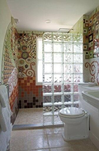 Tijolo de vidro como meio box em banheiro com mosaicos
