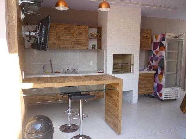 Varanda com churrasqueira com armário de madeira Projeto de Analu Andrade