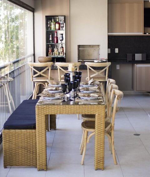 Varanda com churrasqueira com balcão e mesa Projeto de Madi Arquitetura
